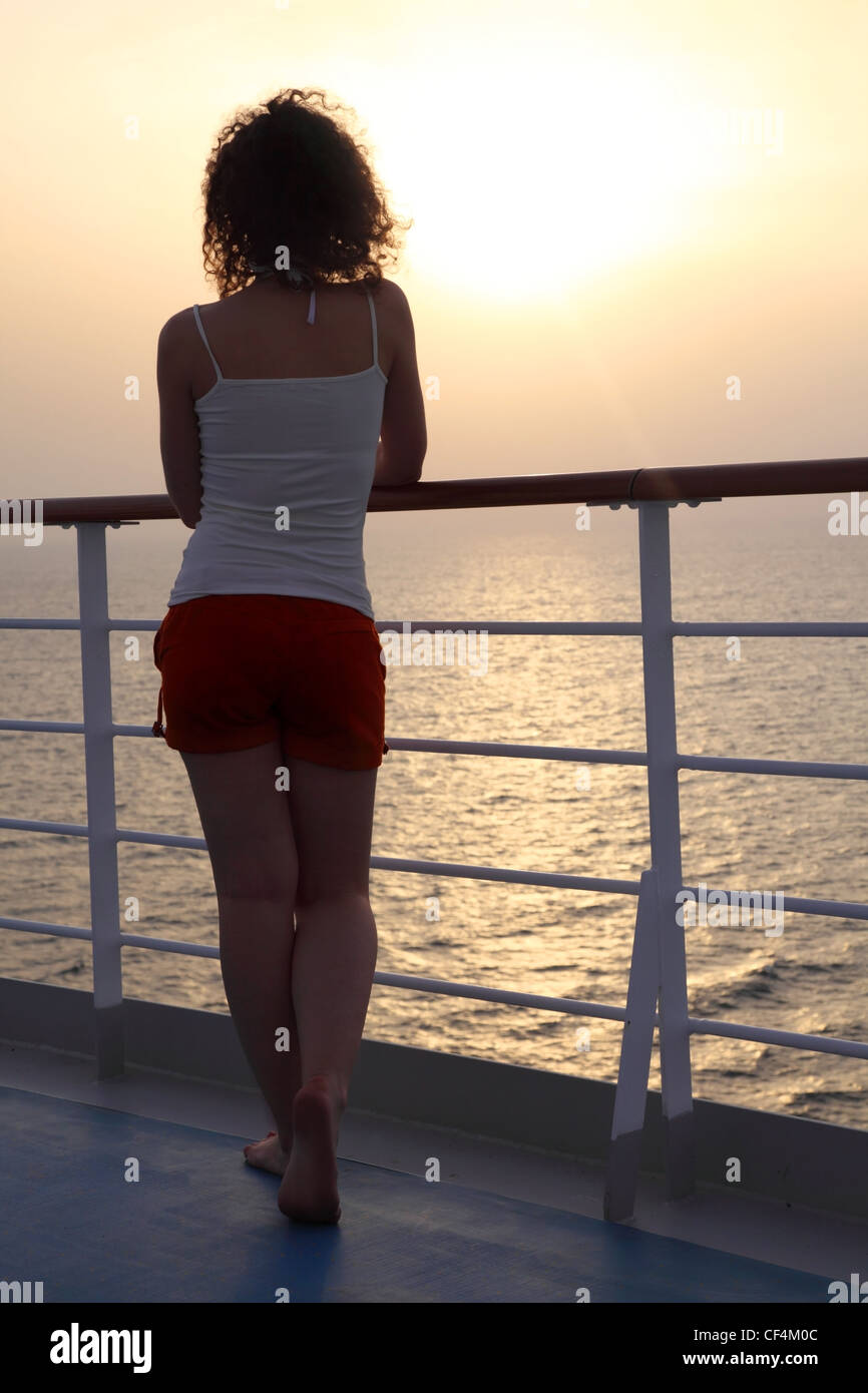 girl standing at ship deck and looking into the distance view from back full body - Stock Image