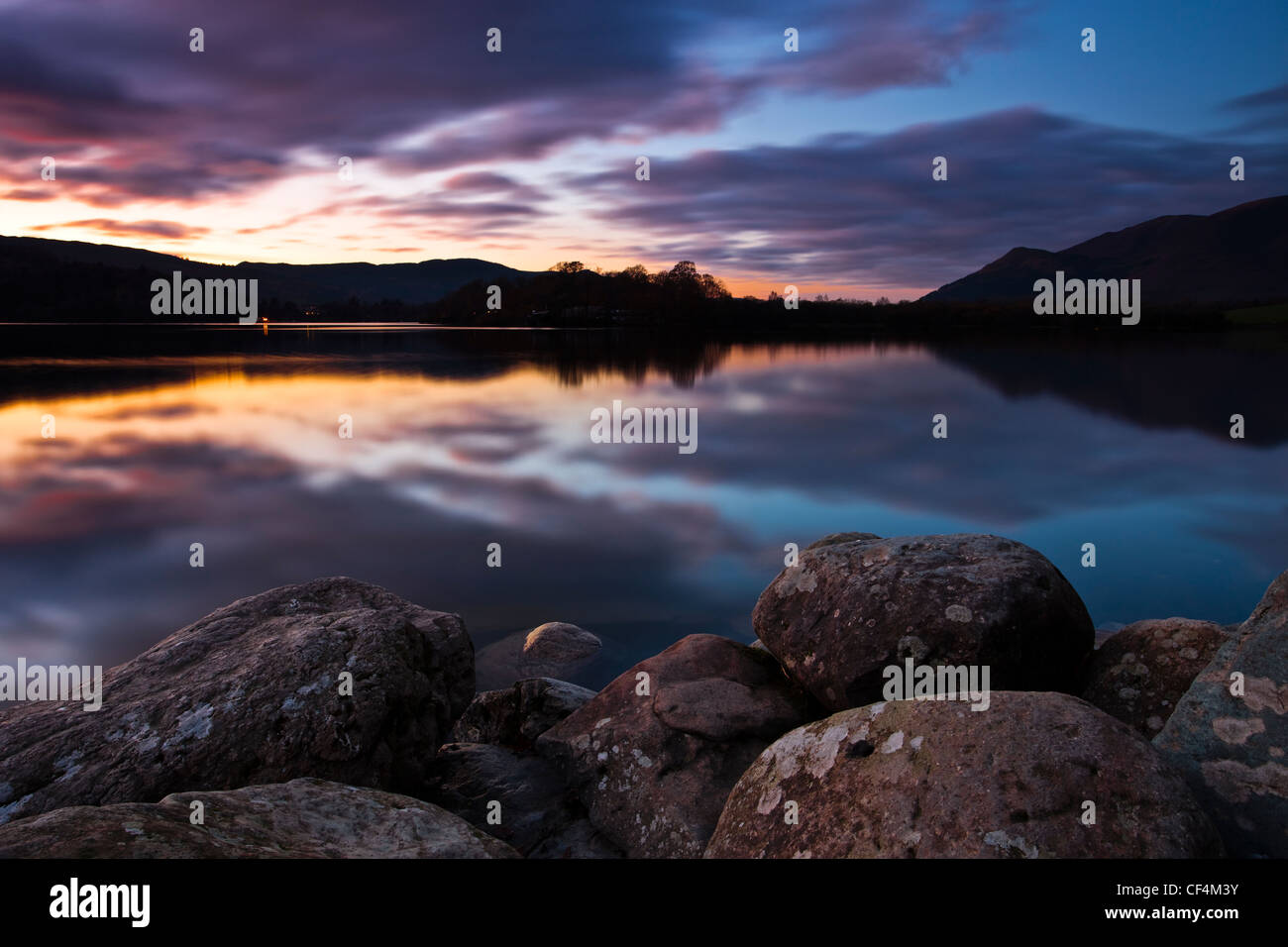 A view over rounded rocks on the shore of Derwentwater at sunset. - Stock Image