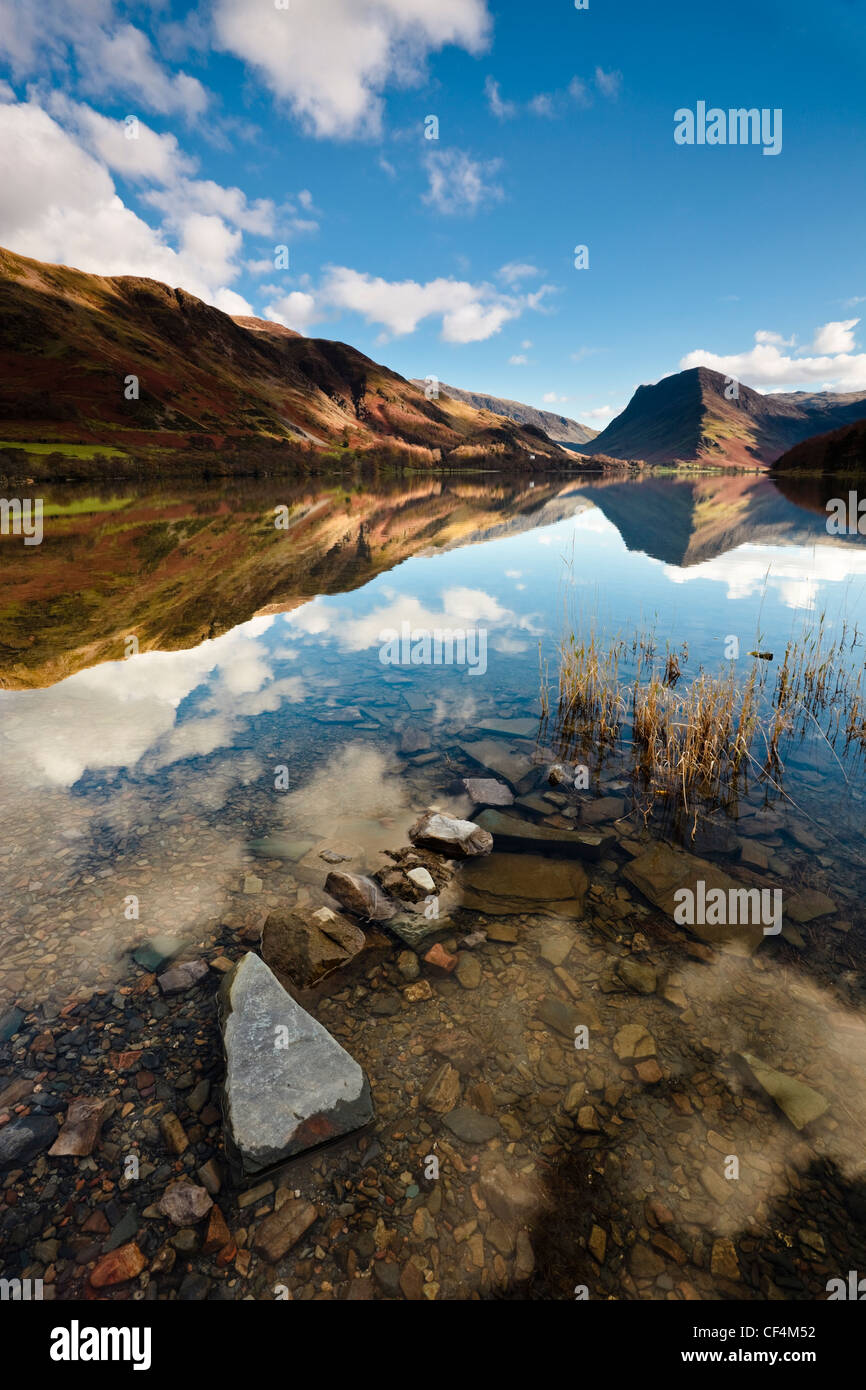The surrounding mountainside reflected in the calm waters of Buttermere lake. Stock Photo