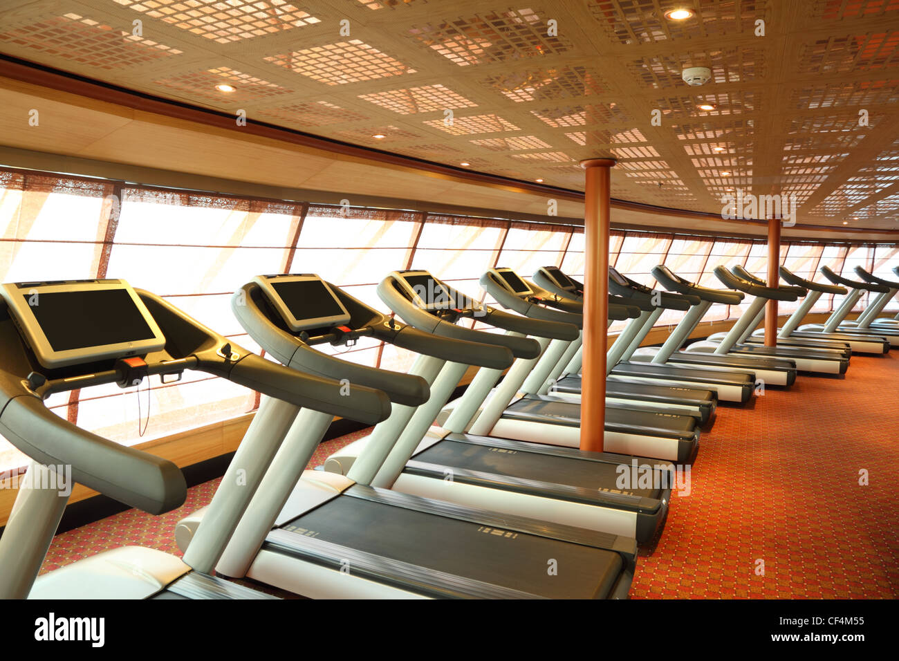 large gym hall with  treadmills near windows in cruise ship general view - Stock Image