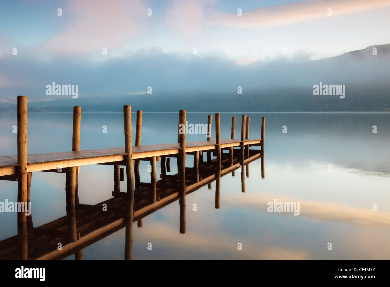 The first rays of sunlight hit the landing jetty at Derwentwater in the Lake District. - Stock Image