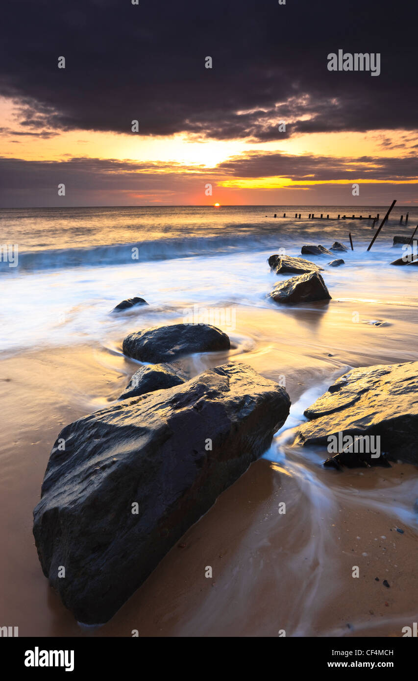 The incoming tide swirls around the rocks of Happisburghs' sea defense. - Stock Image