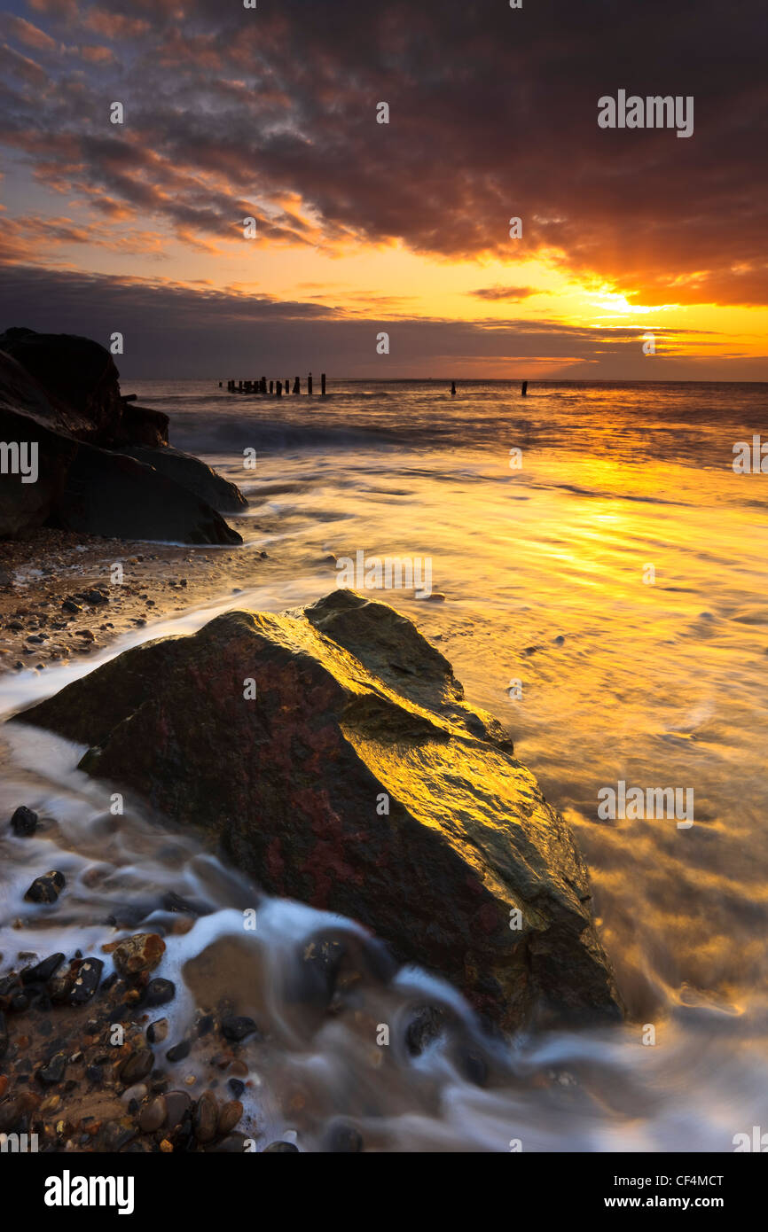 The sun shines through a break in the clouds at sunrise on the Norfolk coast. - Stock Image