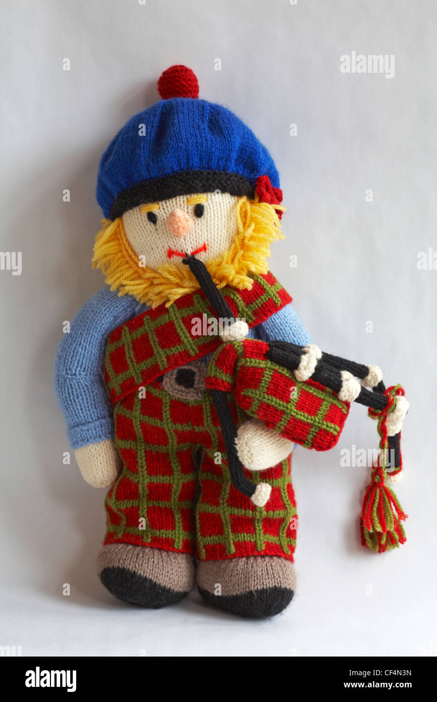 knitted doll - bearded Scot wearing bobble hat and playing the bagpipes isolated on white background - Stock Image