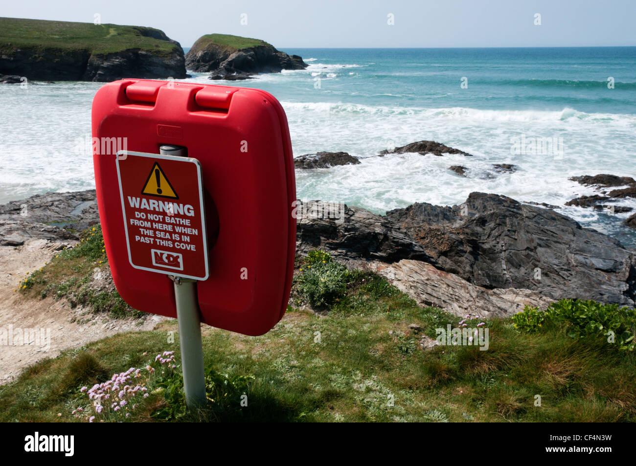 Warning Notice on the back of a lifebelt behind a Cornish beach near Treyarnon Cove. - Stock Image
