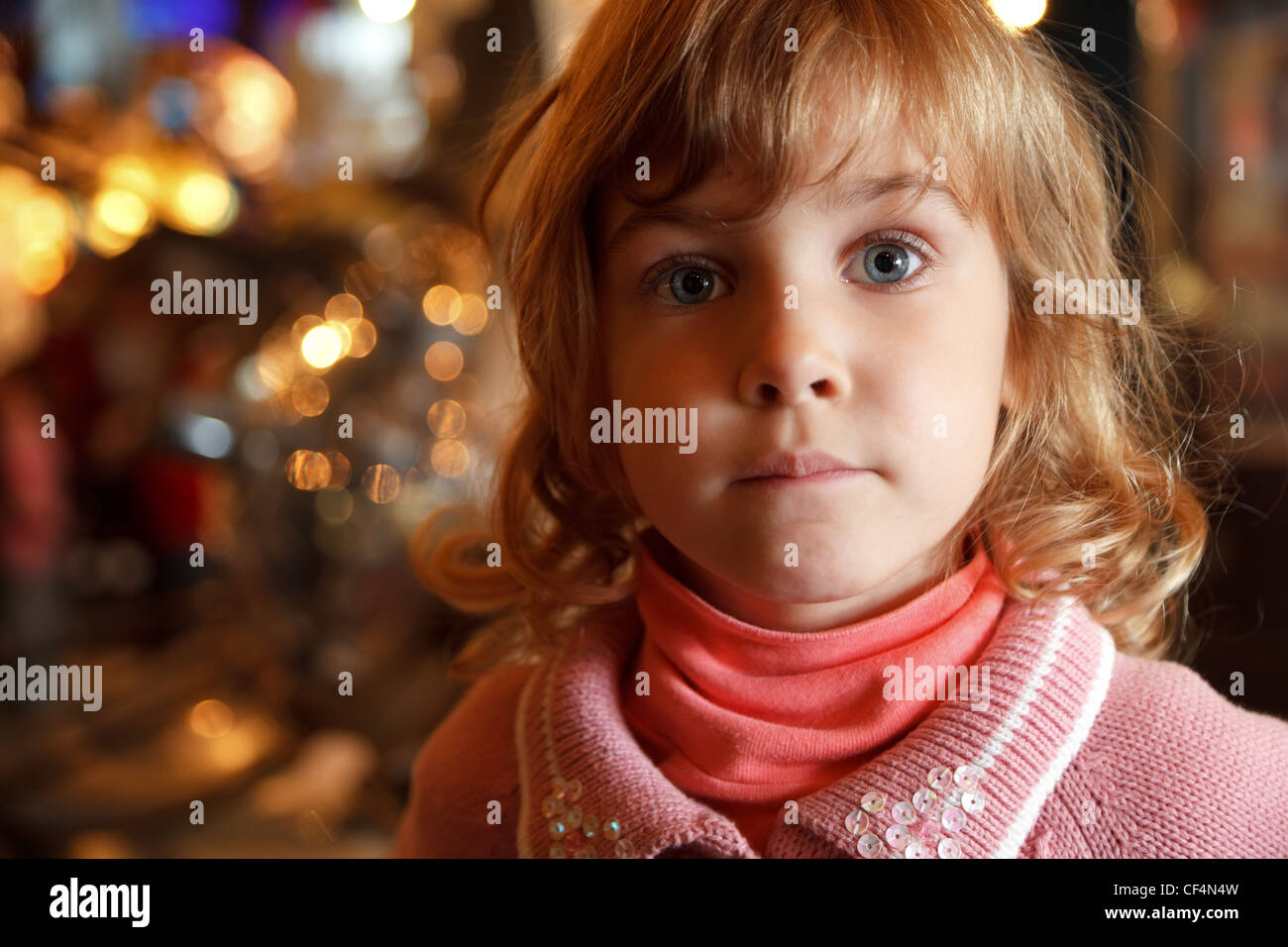 Portrait of charming little girl in background lights. Close-up. Indoors. - Stock Image