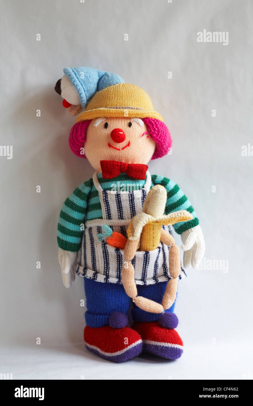 knitted doll with icecream cornet on head and carrot, banana and string of sausages in apron pocket isolated on - Stock Image