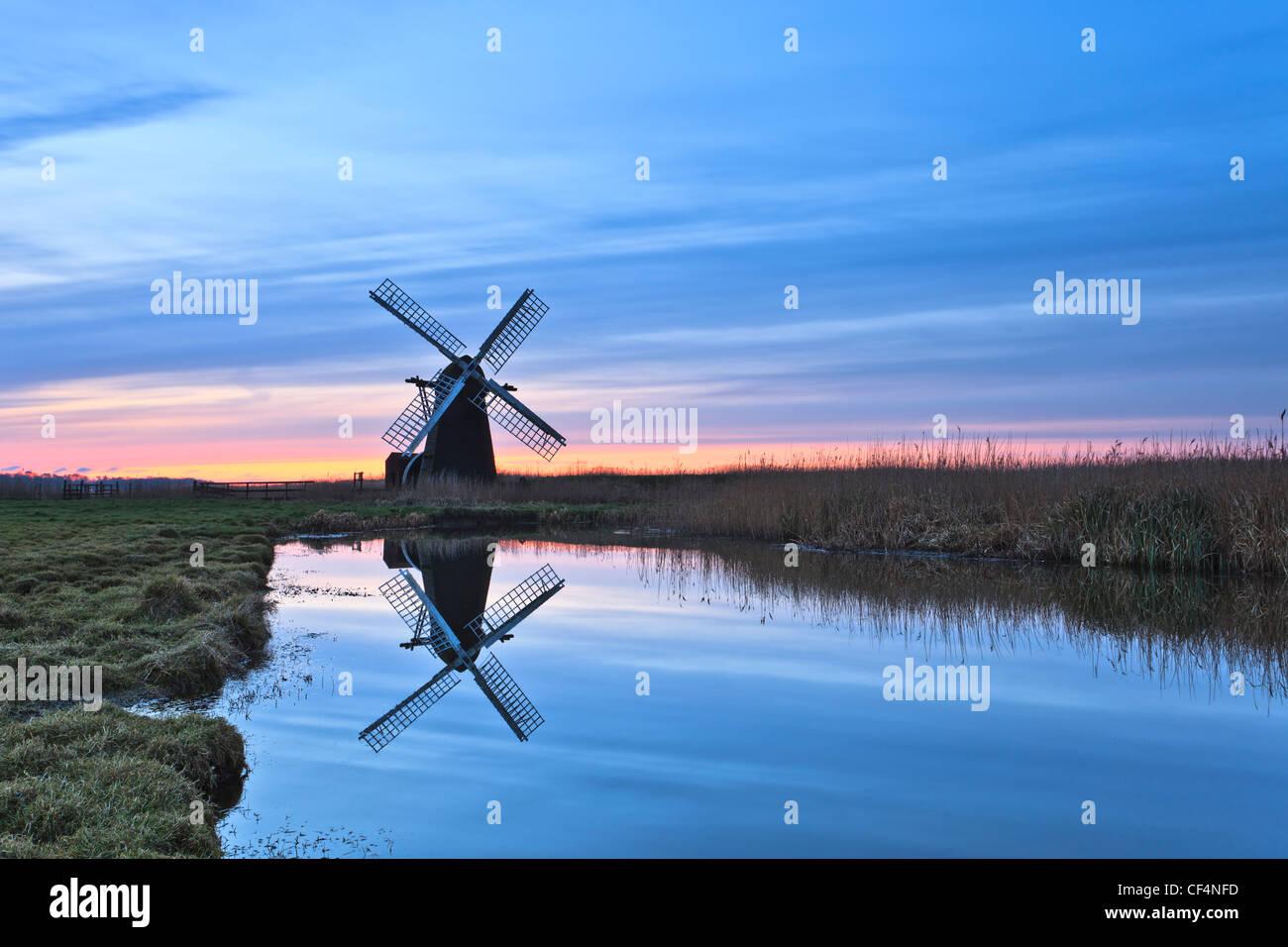 Herringfleet smock mill reflected in still water on a misty winter morning. - Stock Image