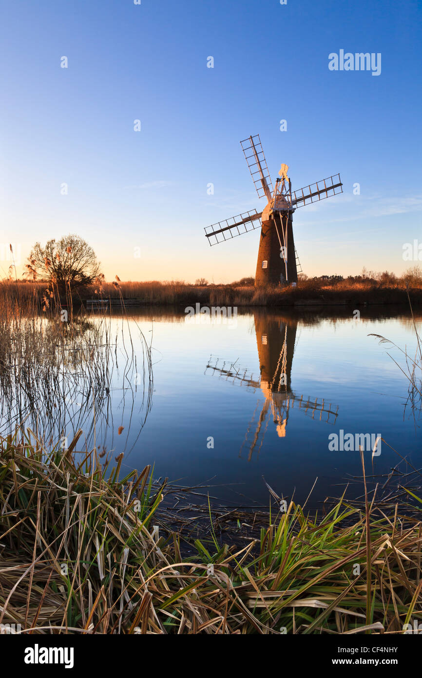 Turf Fen wind pump reflected in still water at How Hill on a winters evening. - Stock Image