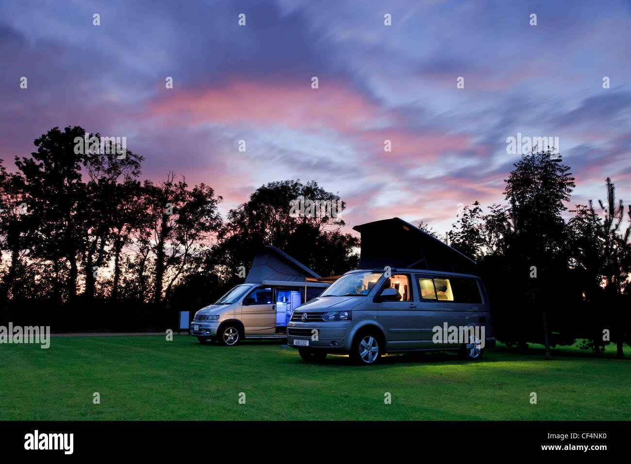 A VW California and a Mazda Bongo, camper vans side by side in a campsite at sunset. - Stock Image