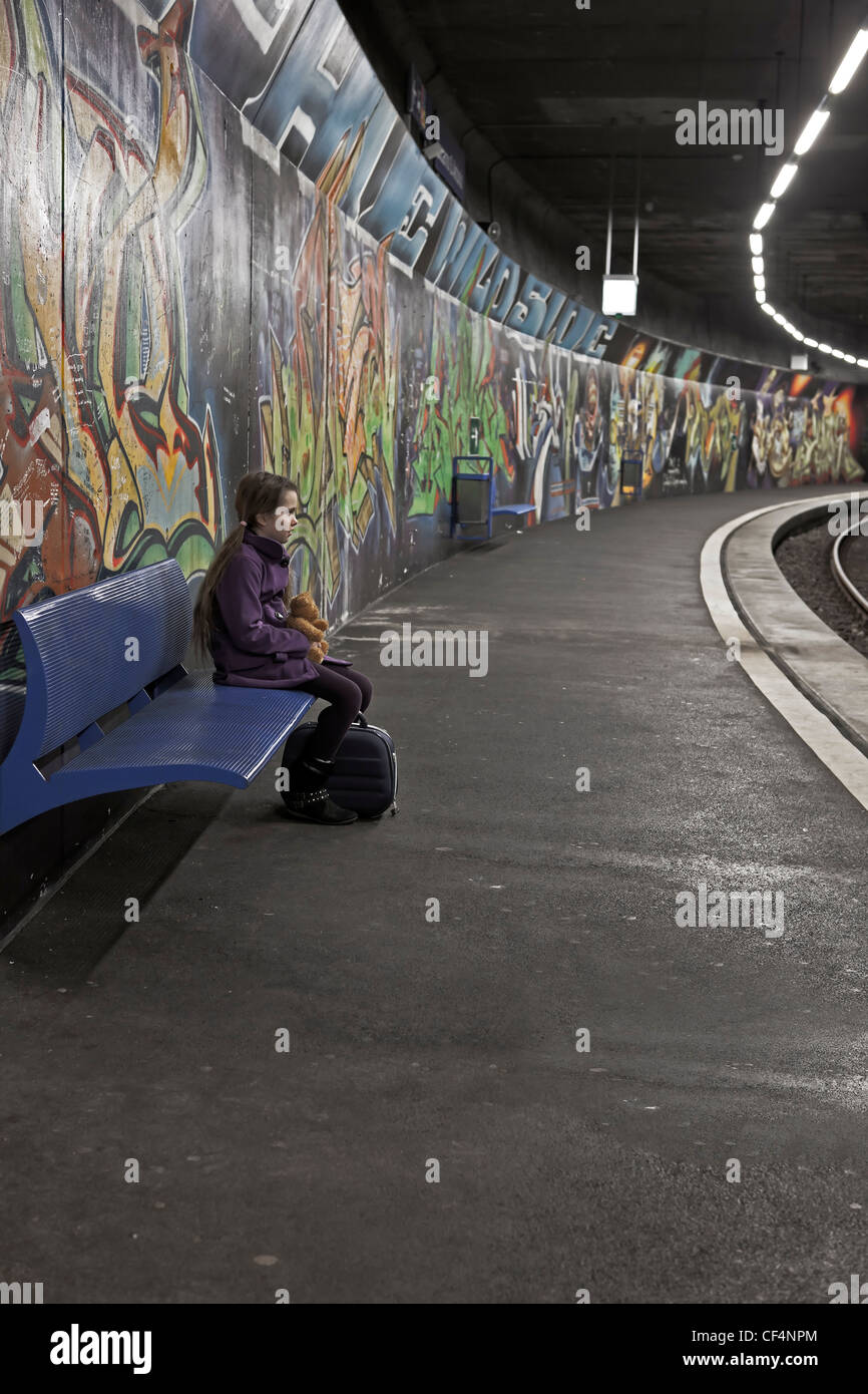 Girl sitting with teddy bear and box on a bench in a subway station with graffiti and waits. - Stock Image