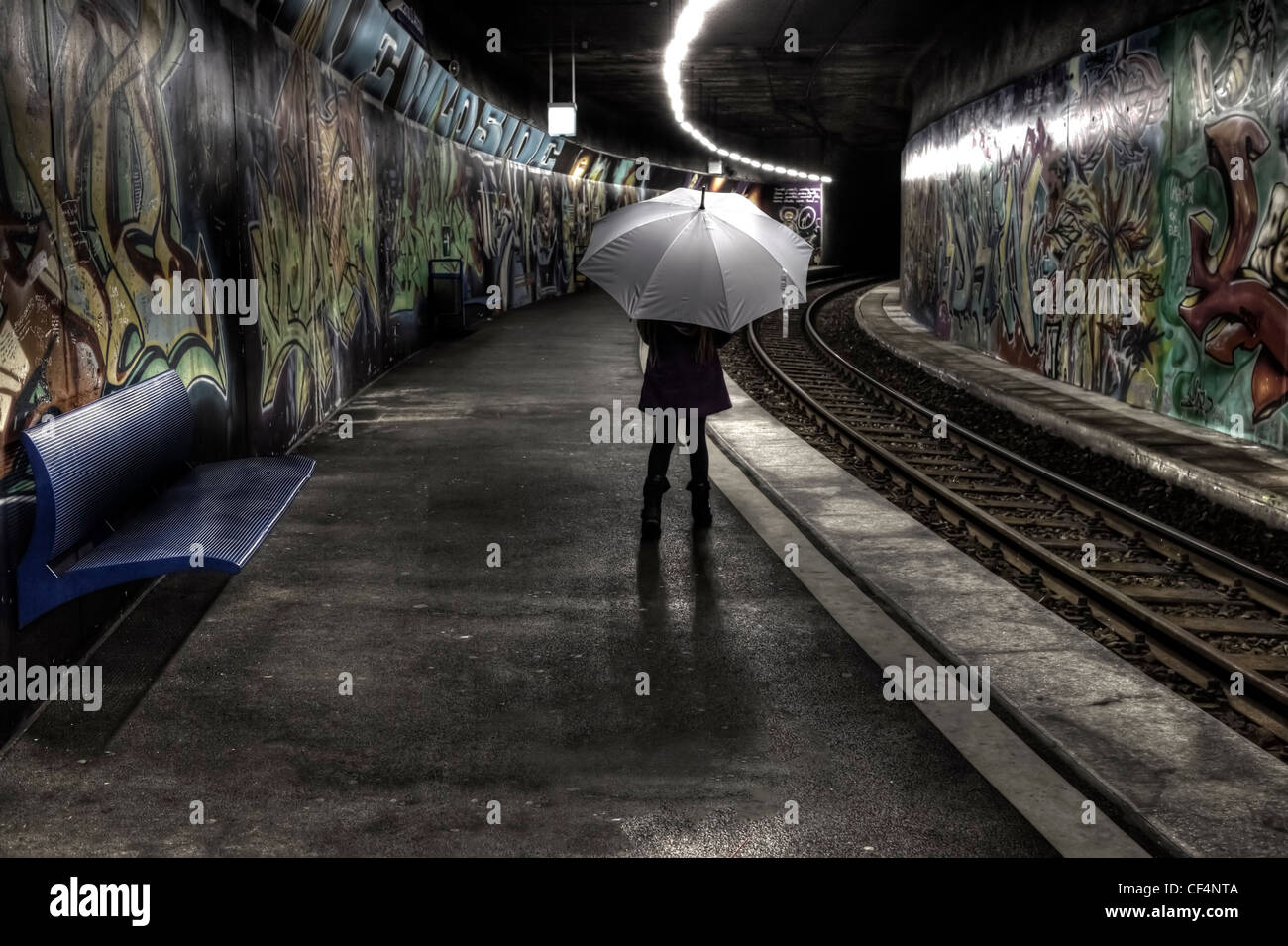 Girl with umbrella stands on a platform at a subway station with graffiti and waits. - Stock Image
