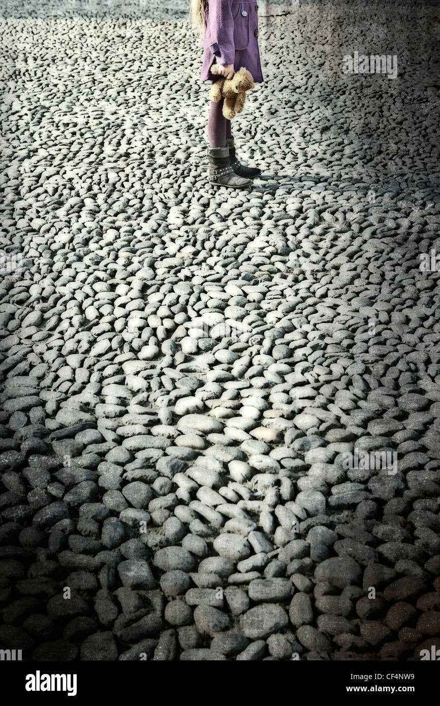 Girl with Teddy on cobblestones - Stock Image