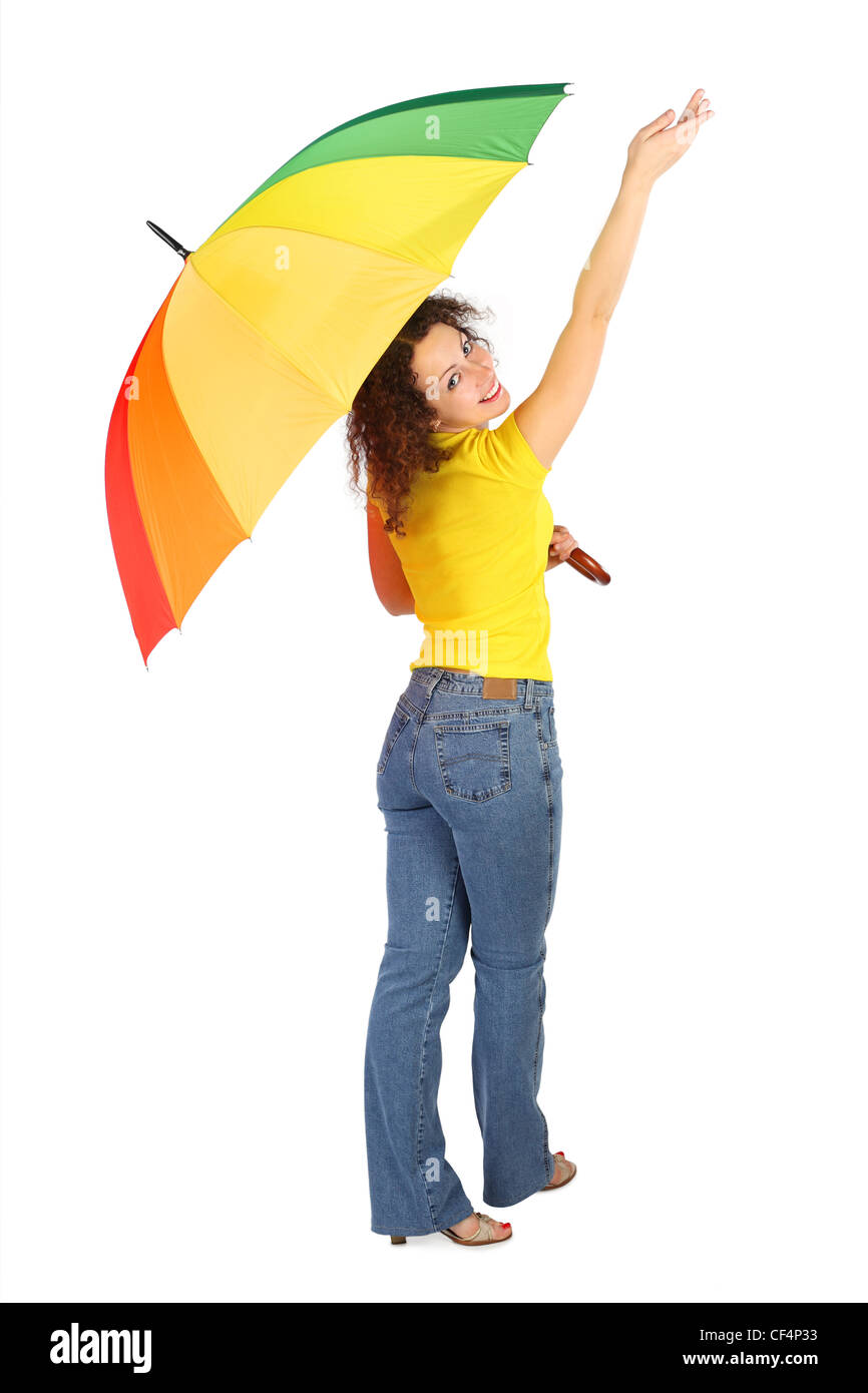 young beauty woman in yellow shirt with multicolored umbrella standing with reached out a hand isolated on white, - Stock Image