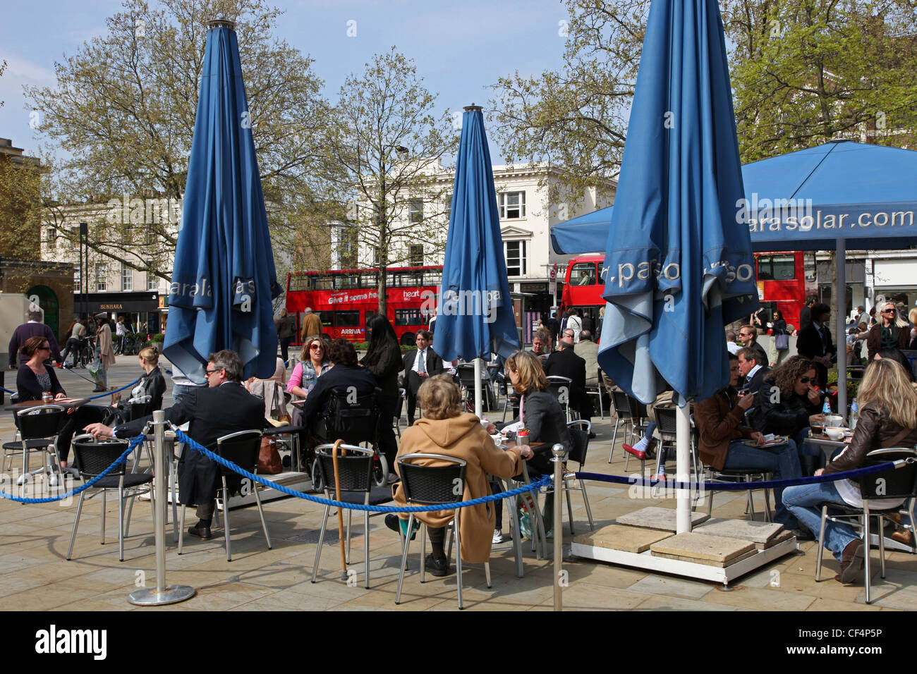 People sitting at tables at a pavement cafe on the King's Road in Chelsea. Stock Photo
