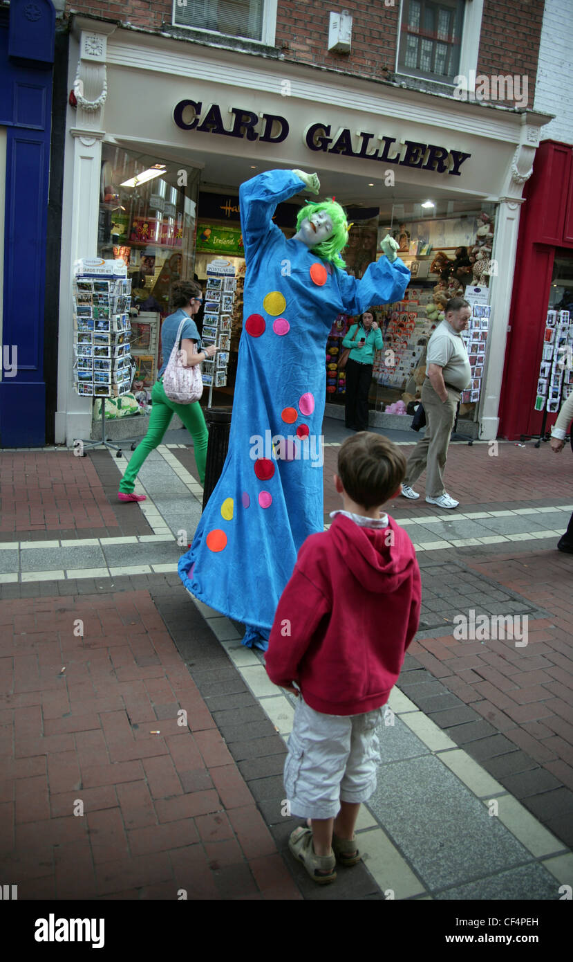 A small boy is entranced by a street entertainer performing in Grafton Street. - Stock Image