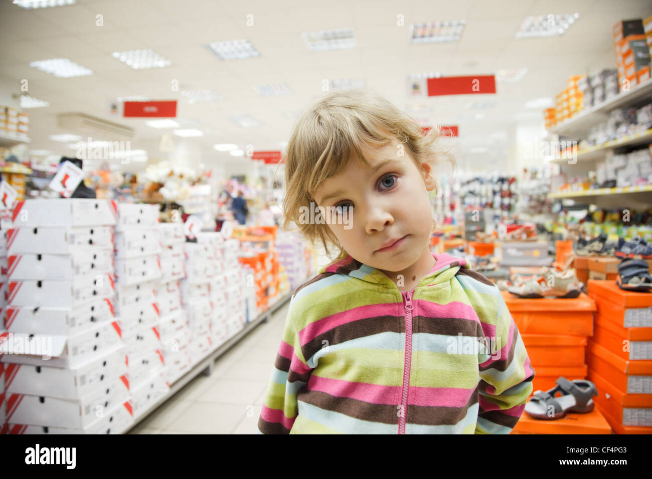 little girl in supermarket alone, chooses in department footwear - Stock Image