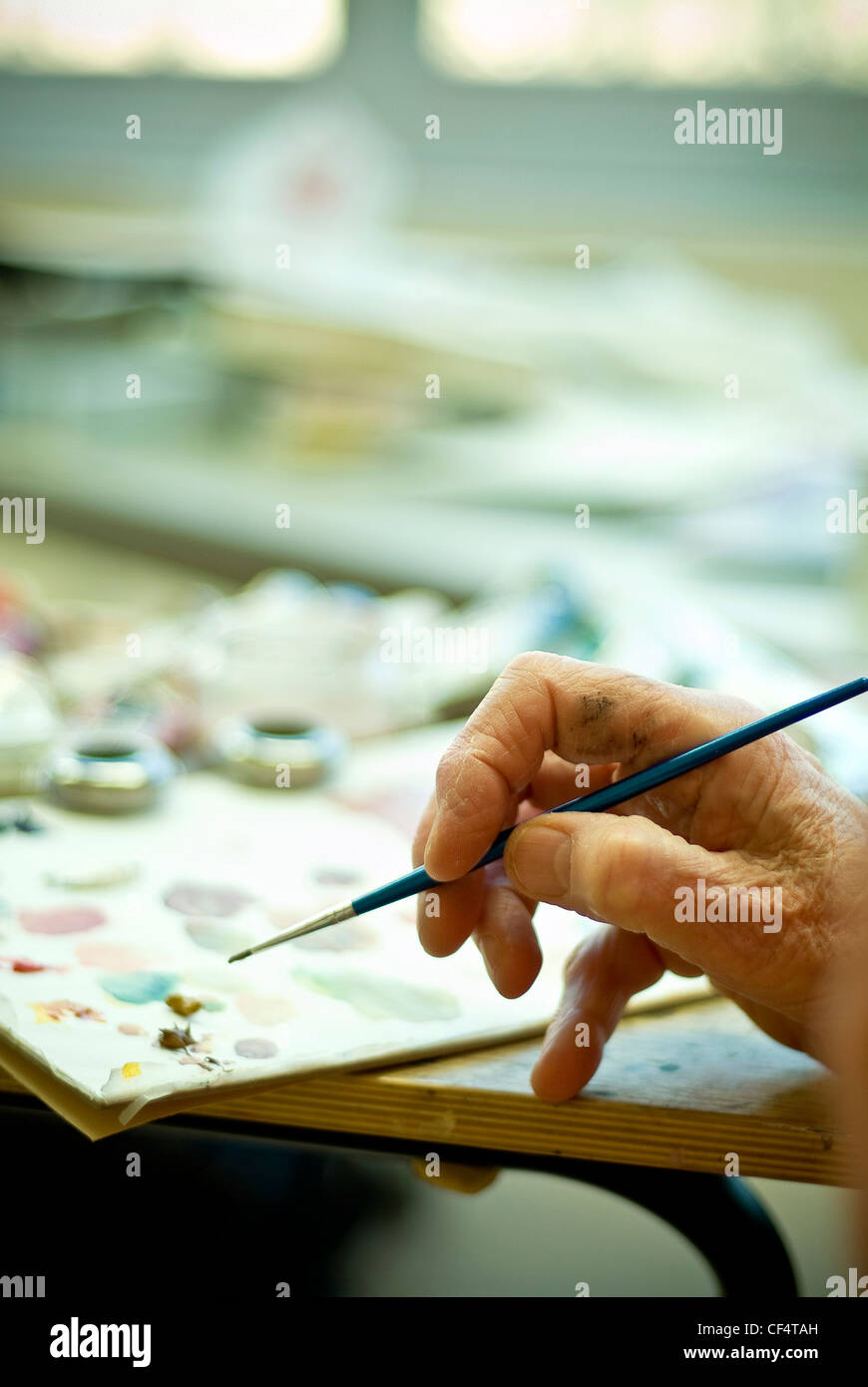 Artist applying brush strokes on an oil painting - Stock Image