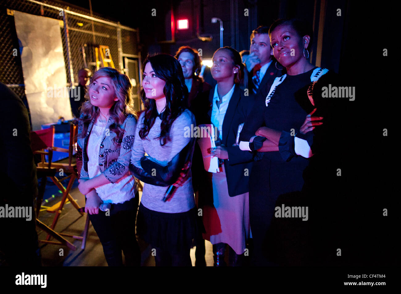 First Lady Michelle Obama watches a performance backstage with iCarly cast members Jennette McCurdy, left, and Miranda - Stock Image