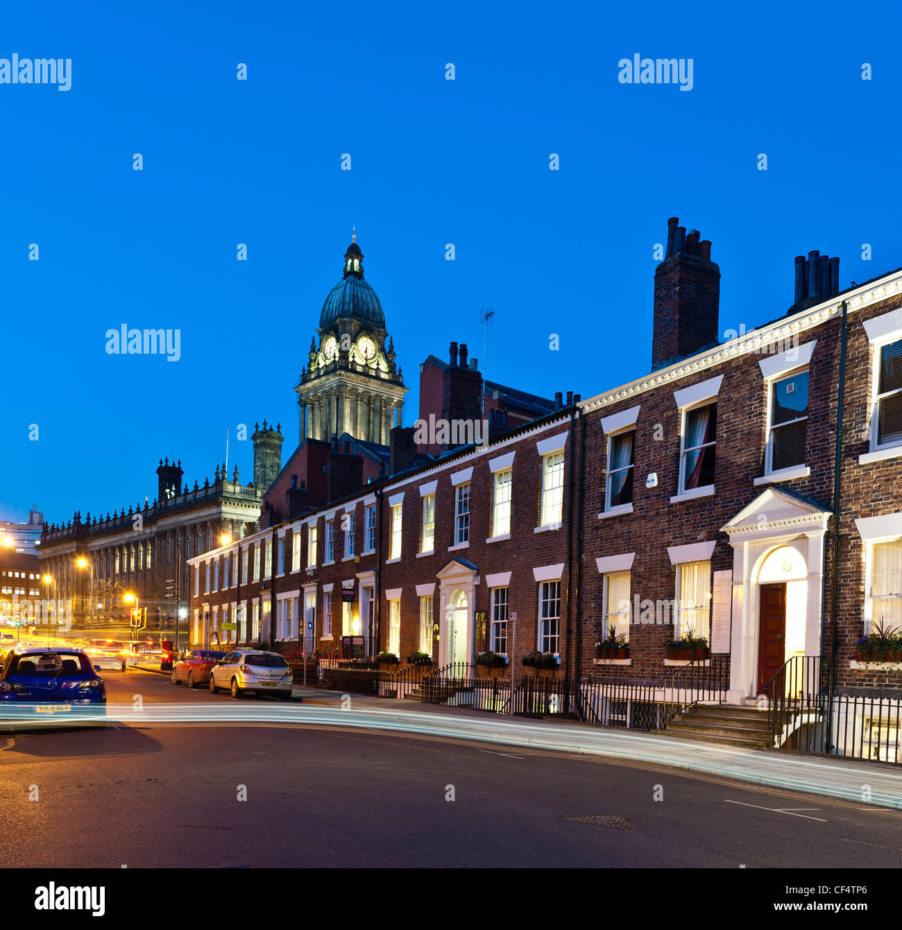 Leeds Town Hall and Georgian terrace houses at night with light trail of passing car. - Stock Image