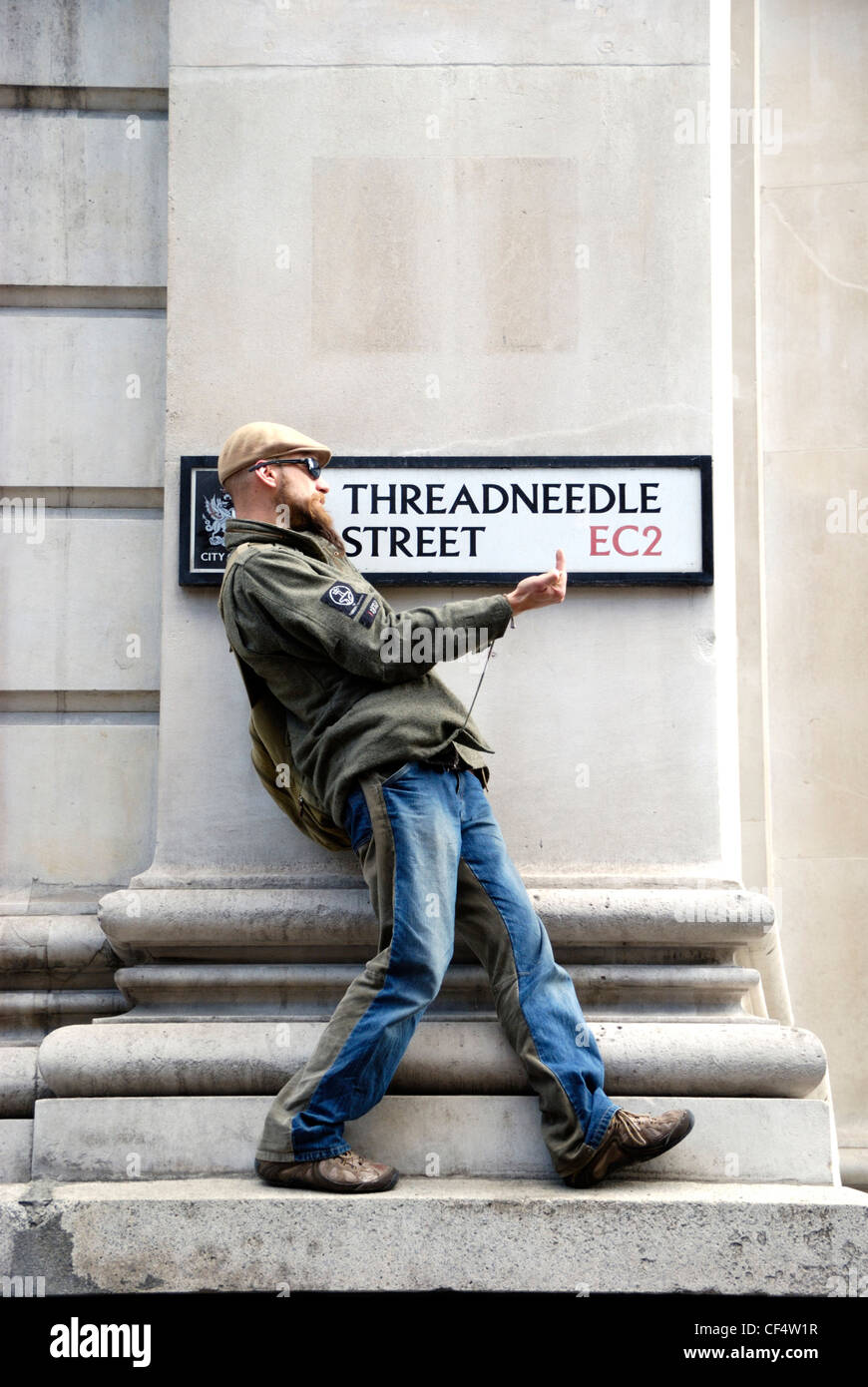 A young male protestor making a rude gesture in front of a Threadneedle Street sign during the G20 demonstrations - Stock Image