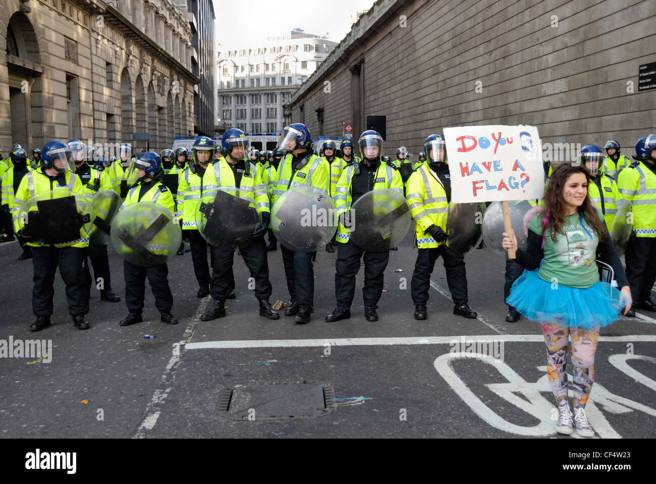 A young female protestor wearing a tutu and holding up a placard in front of a line of riot police during the G20 - Stock Image