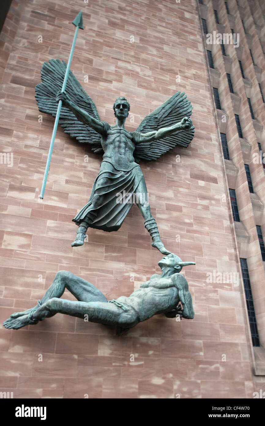 Sculptures of St Michael and the Devil at the entrance to the new Coventry Cathedral which celebrates its Golden - Stock Image