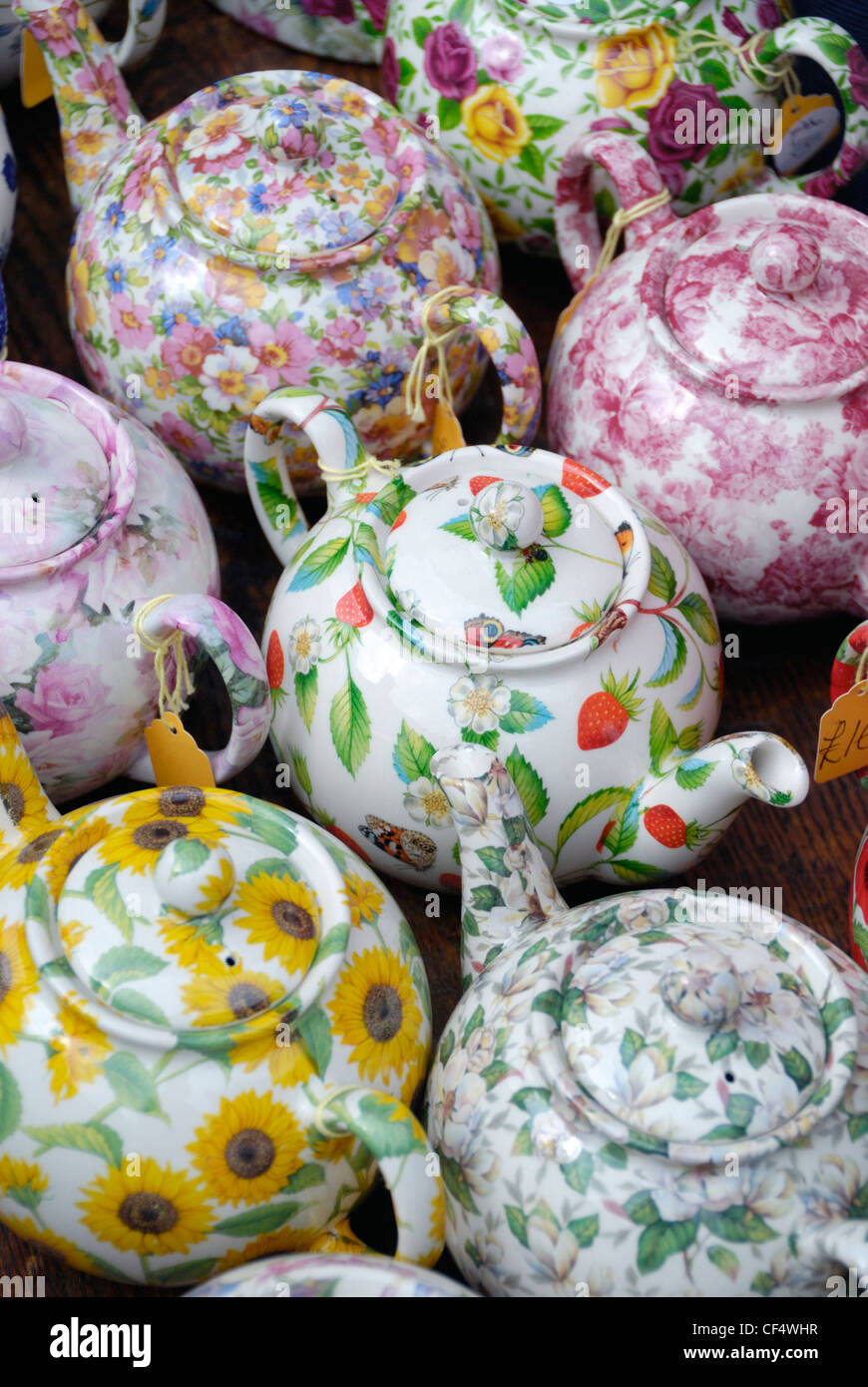 Colourful English China teapots displayed on a market stall in Portobello Road. - Stock Image