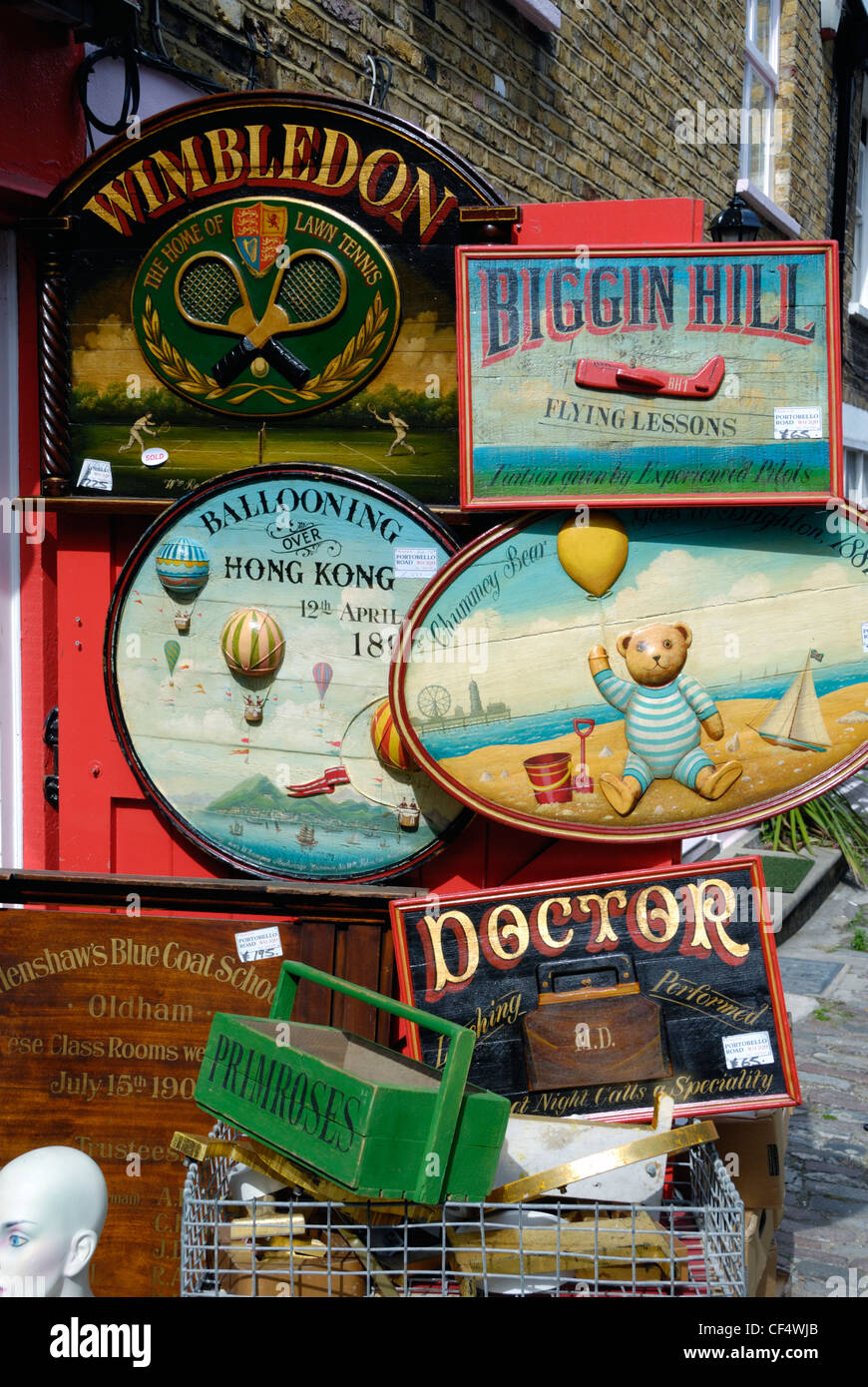 Lots of old hand painted wooden advertising signs for sale outside an antiques shop in portobello road