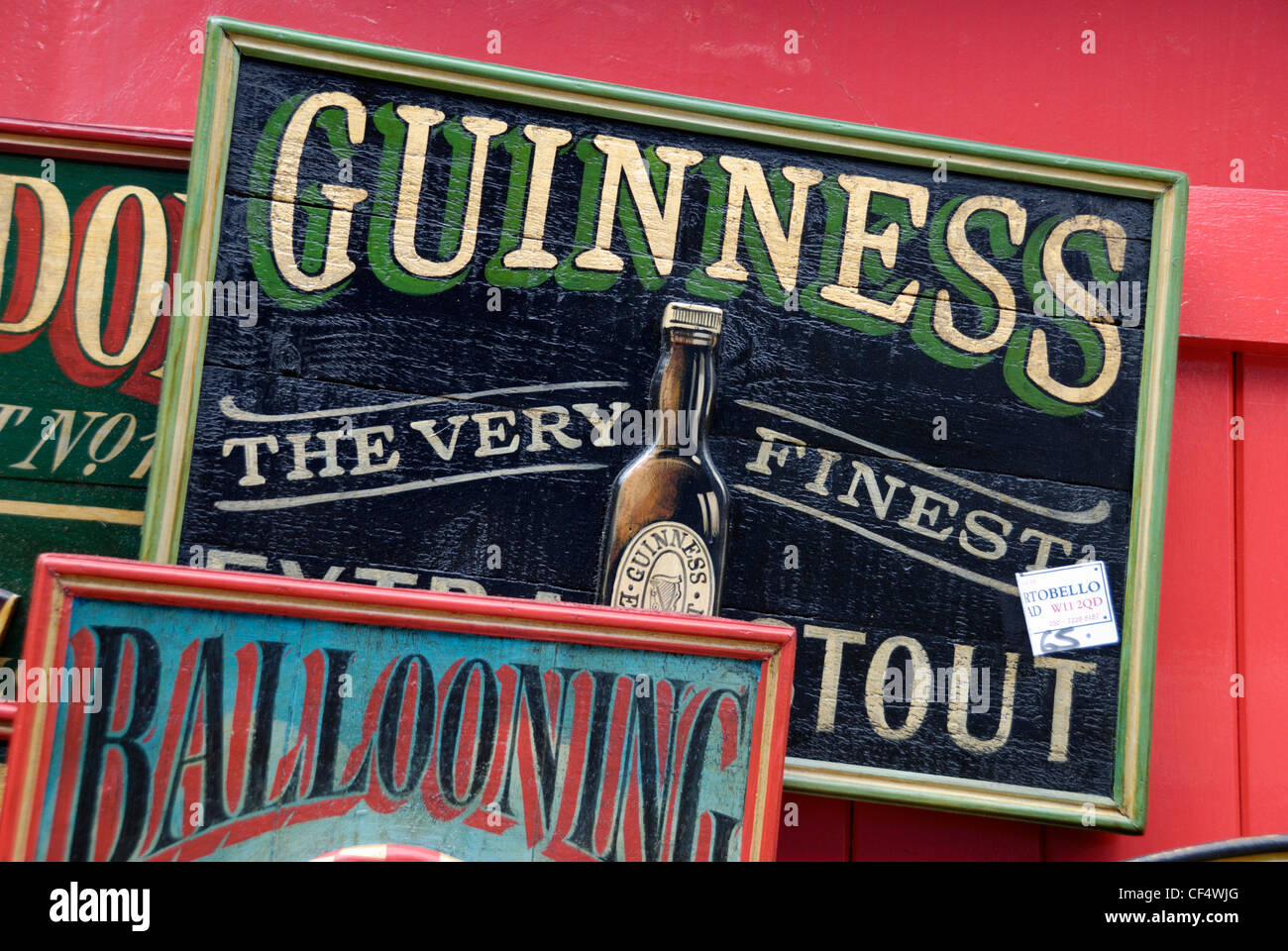 An old wooden hand painted guinness advertising sign for sale ouside an antiques shop in portobello road