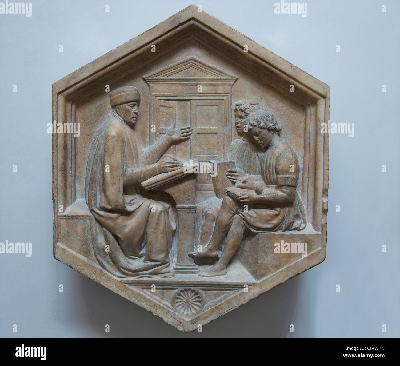 Grammar with Priscian or Donatus teaching two boys, by Luca della Robbia, original relief from the Campanile, Museo - Stock Image