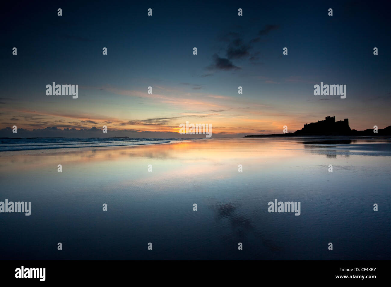 Early dawn light reflected in the glistening shore by Bamburgh Castle. - Stock Image