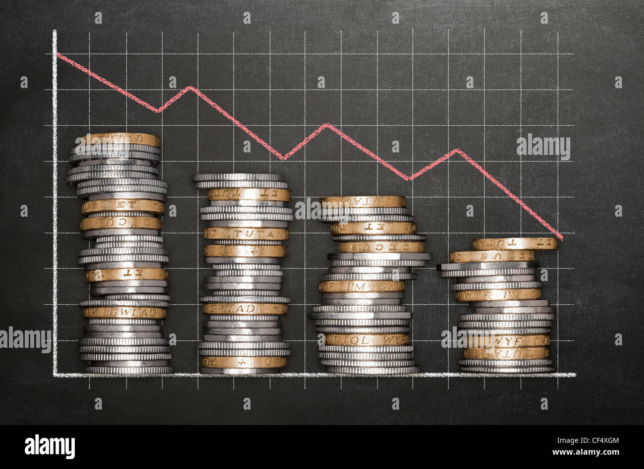Stacks of coins on a blackboard background forming a graph - Stock Image