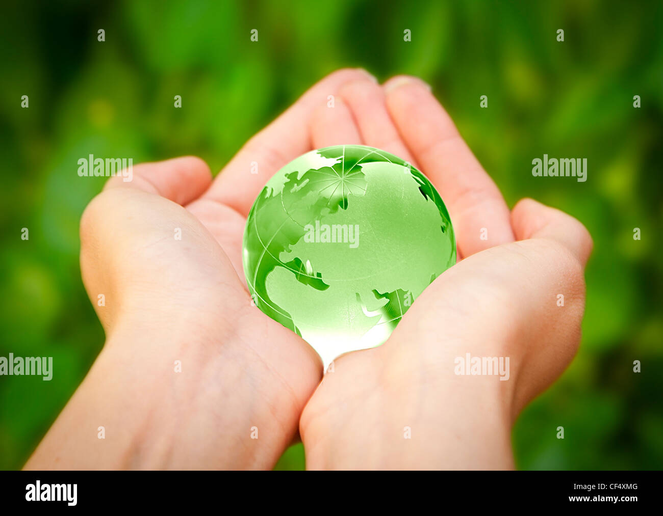 human hands carefully holding Earth planet. Glass World - Stock Image