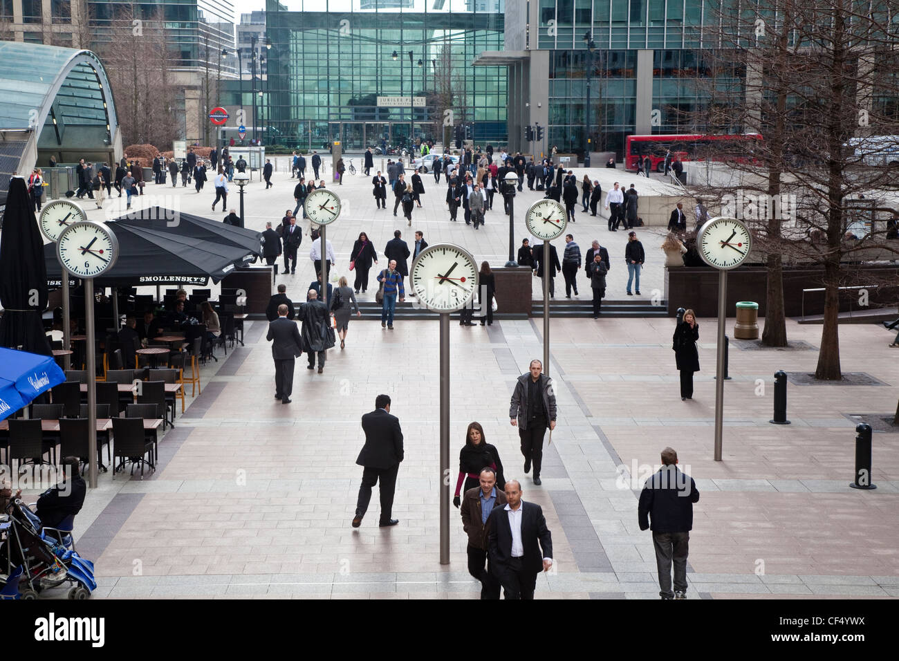 Business men and women walking through Reuters Plaza past a series of six dual faced clocks by Konstantin Grcic, Stock Photo