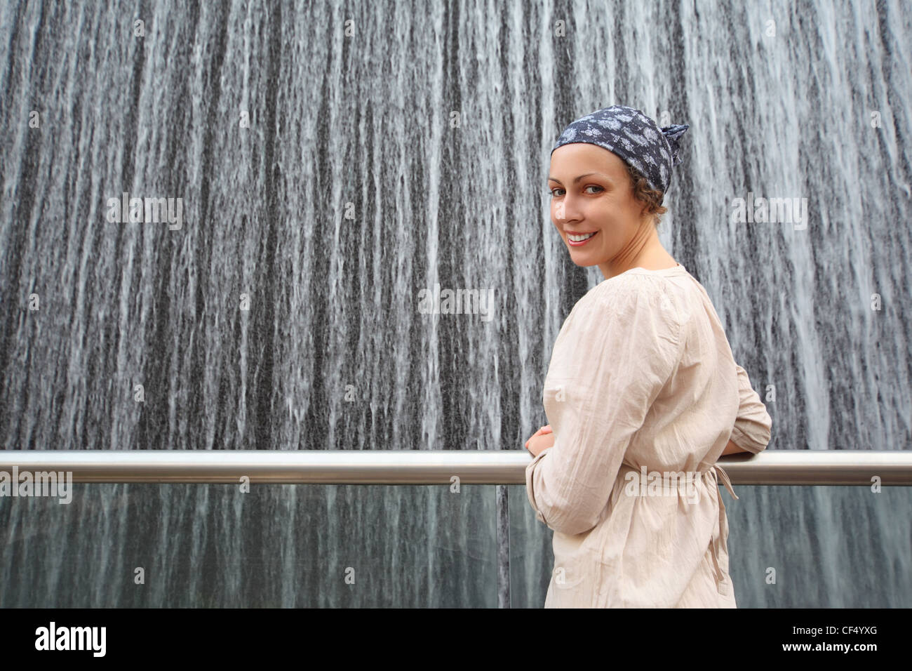 young beauty woman in white shirt standing near big fountain and looking back, half body - Stock Image