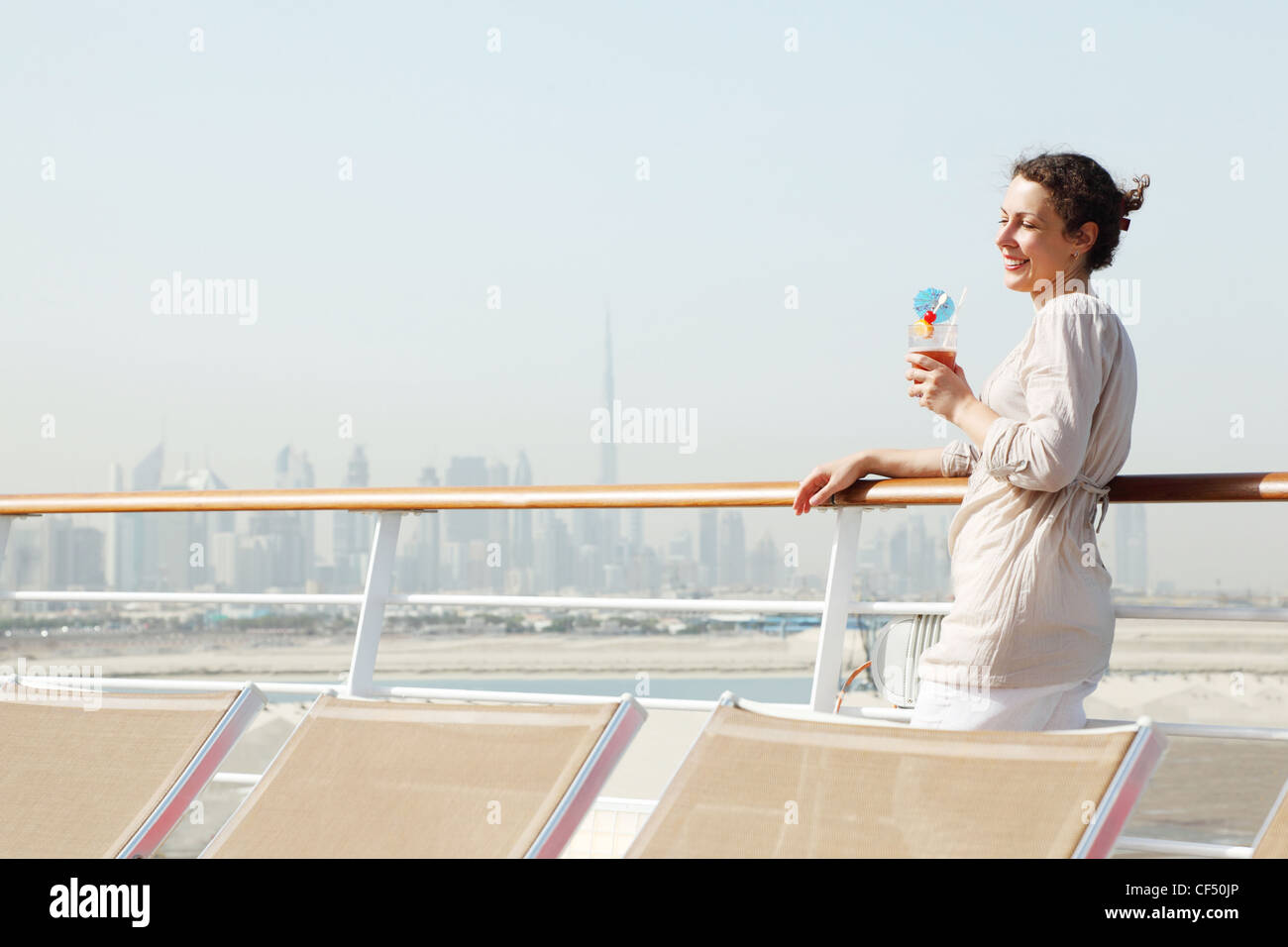 young beauty woman with cocktail standing on cruise liner deck, half body - Stock Image