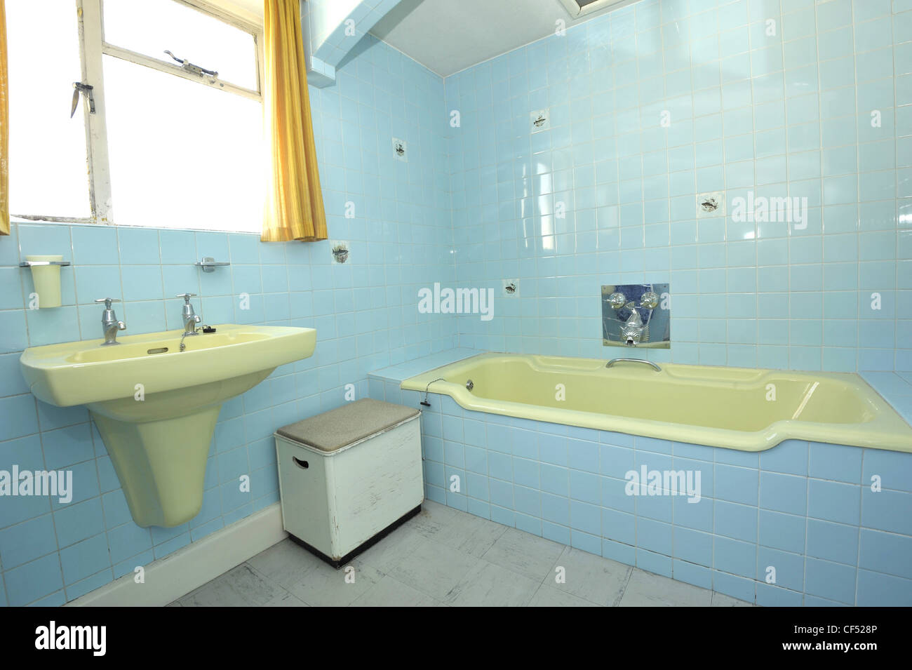 A dated bathroom with light green suite and blue tiling Stock Photo ...