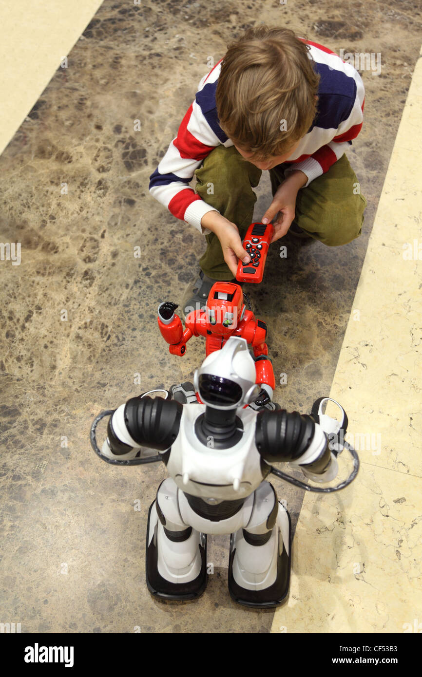 little boy playing with two radio controlled robots view from above Stock Photo
