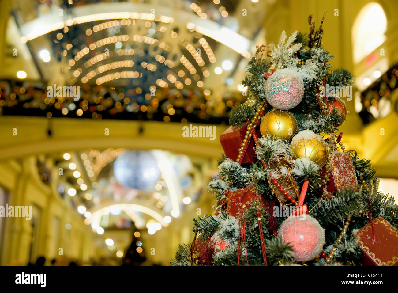 Fur-tree densely covered by Christmas ornaments in shopping centre - Stock Image
