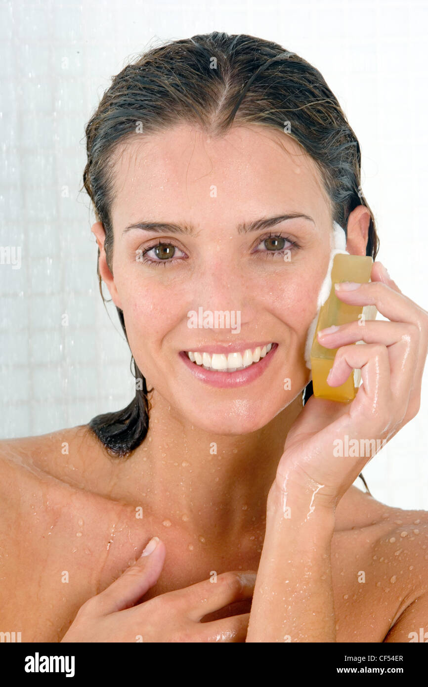 female with long wet brunette hair standing in shower holding bar of