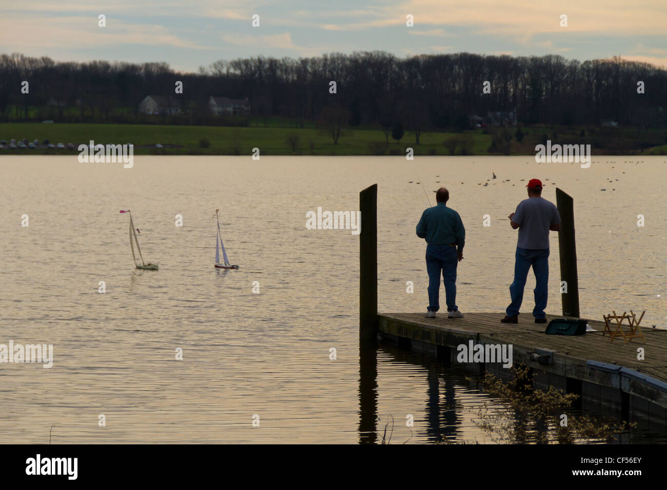 Two men operating radio-controlled boats on a lake - Stock Image