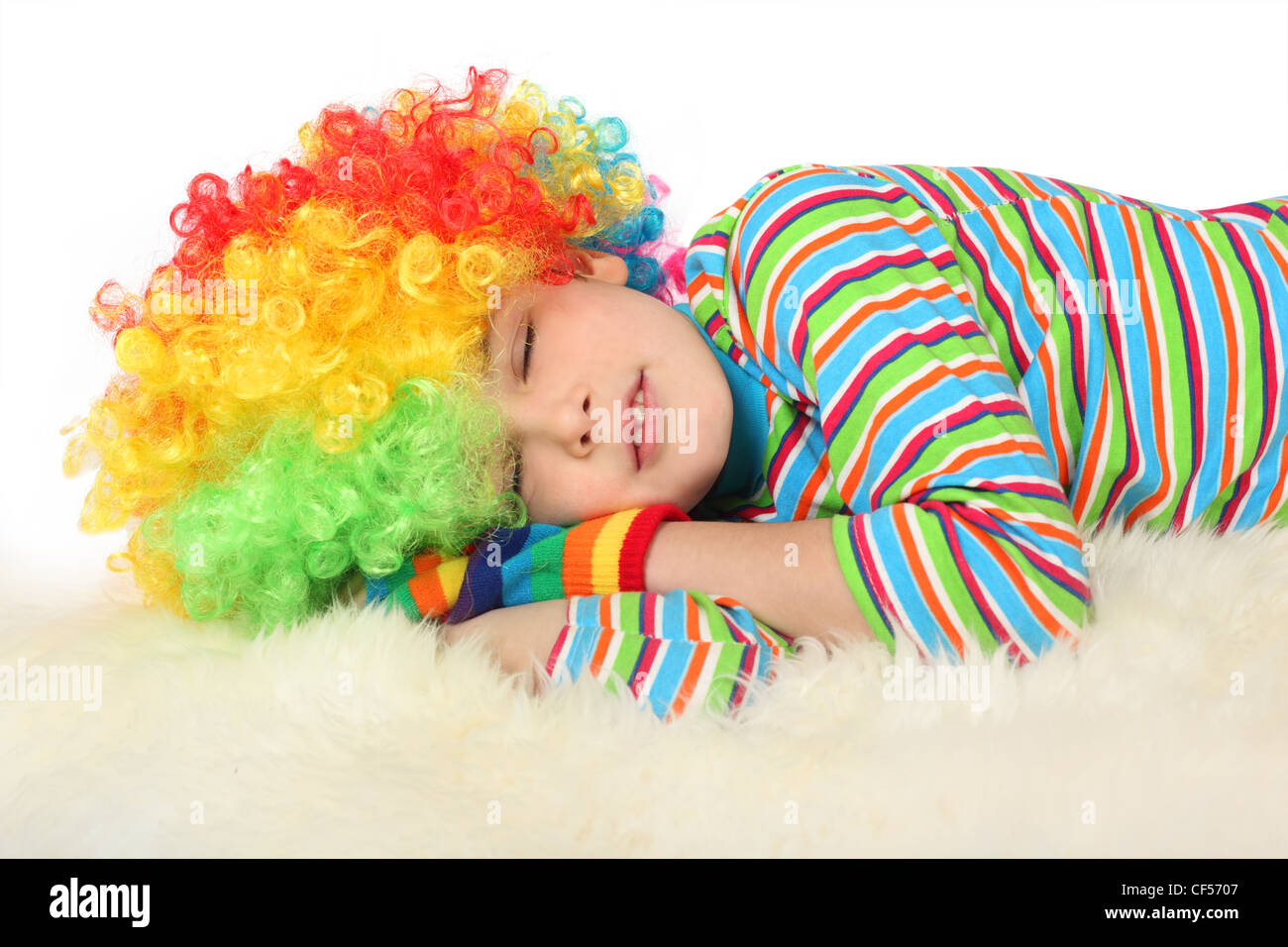 boy in clown dress sleeping isolated on white background Stock Photo
