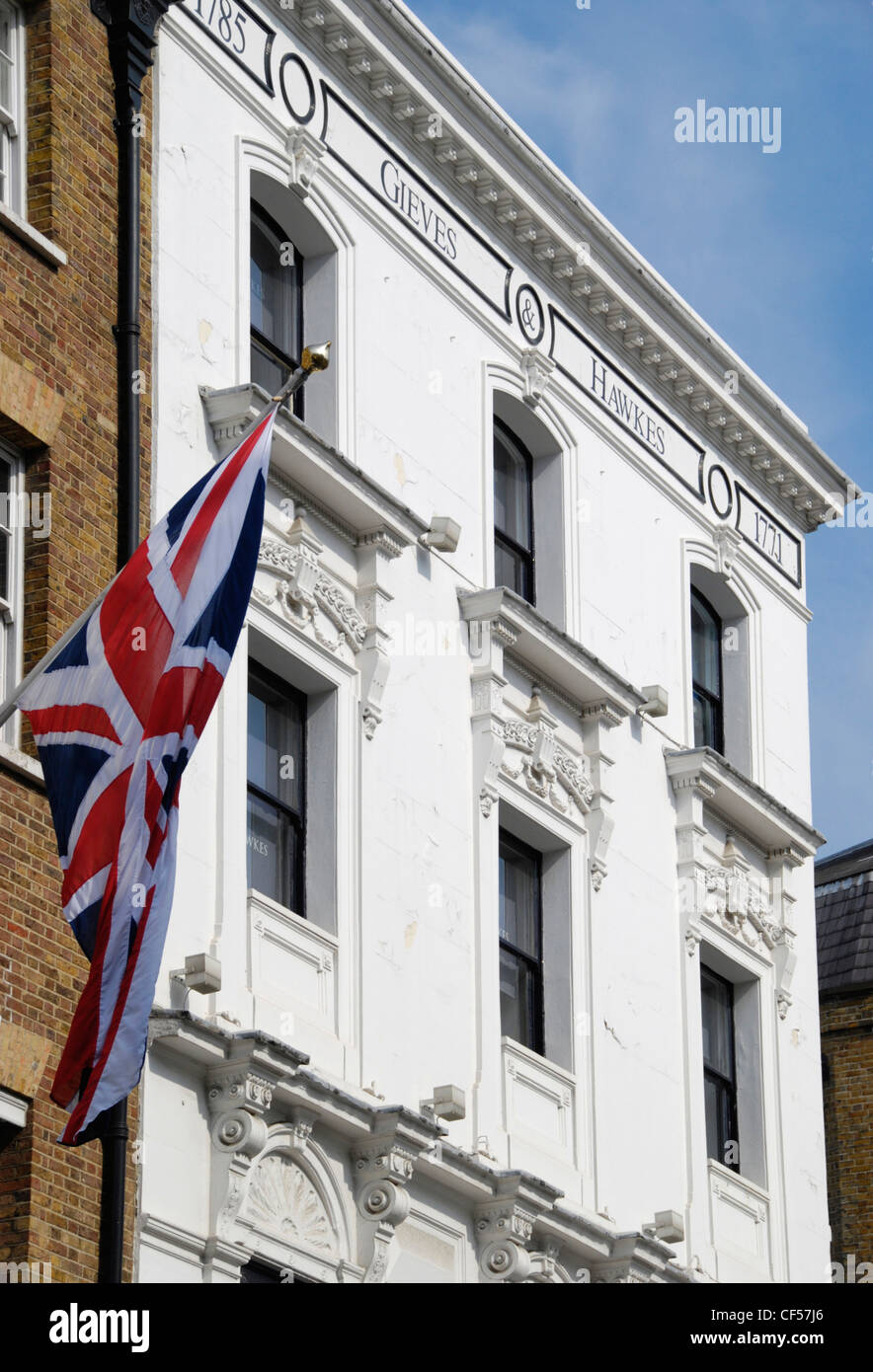 A British flag hangs above Gieves and Hawkes tailors on Saville Row. - Stock Image