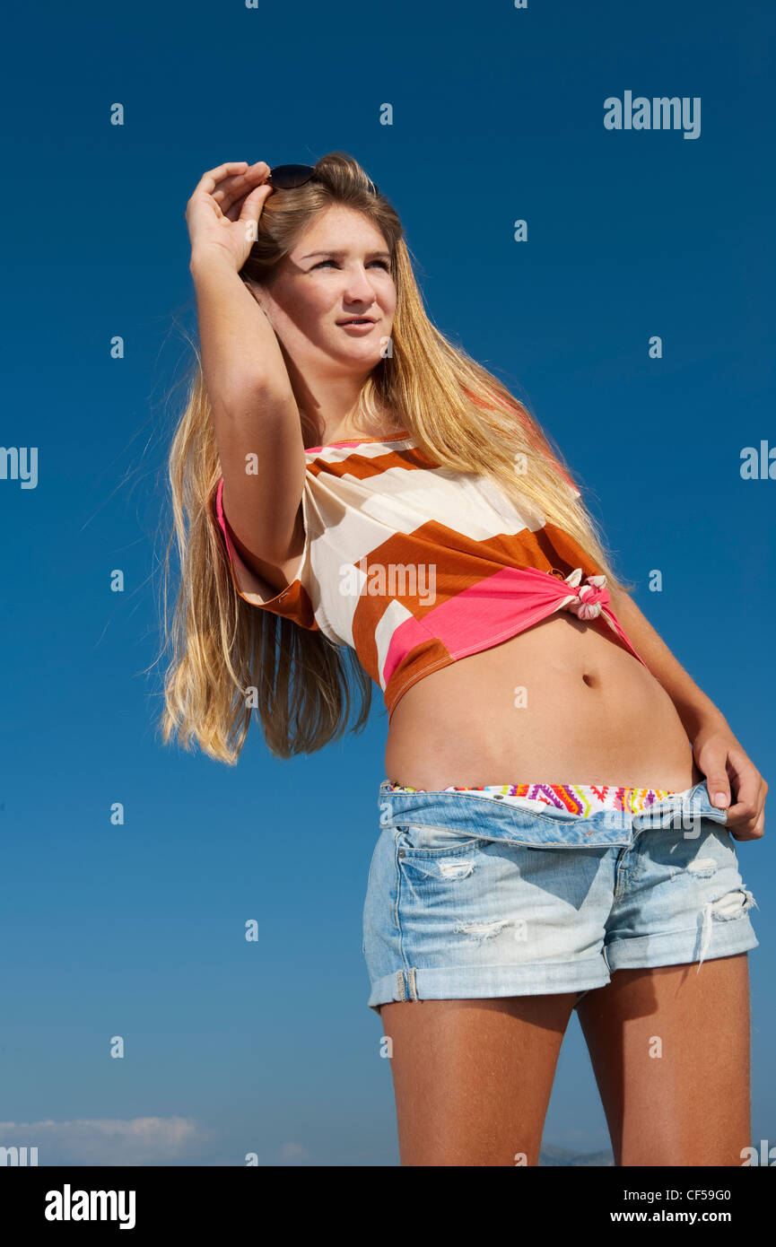 Pretty young woman relaxing by the sea on a sunny day in Alcudia, Majorca. - Stock Image