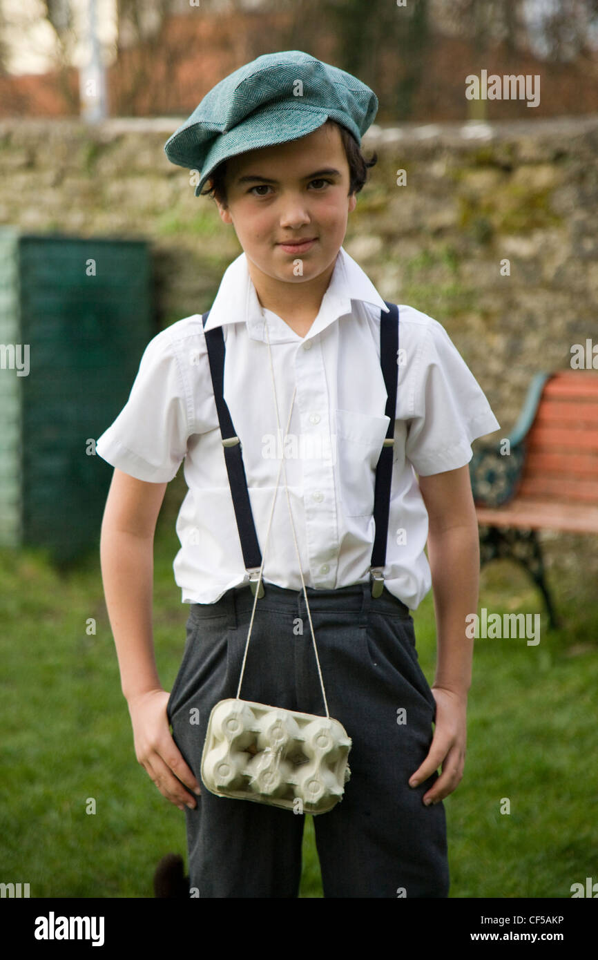Schoolboy dressed in 1940s costume with egg box as gas mask case - Stock Image