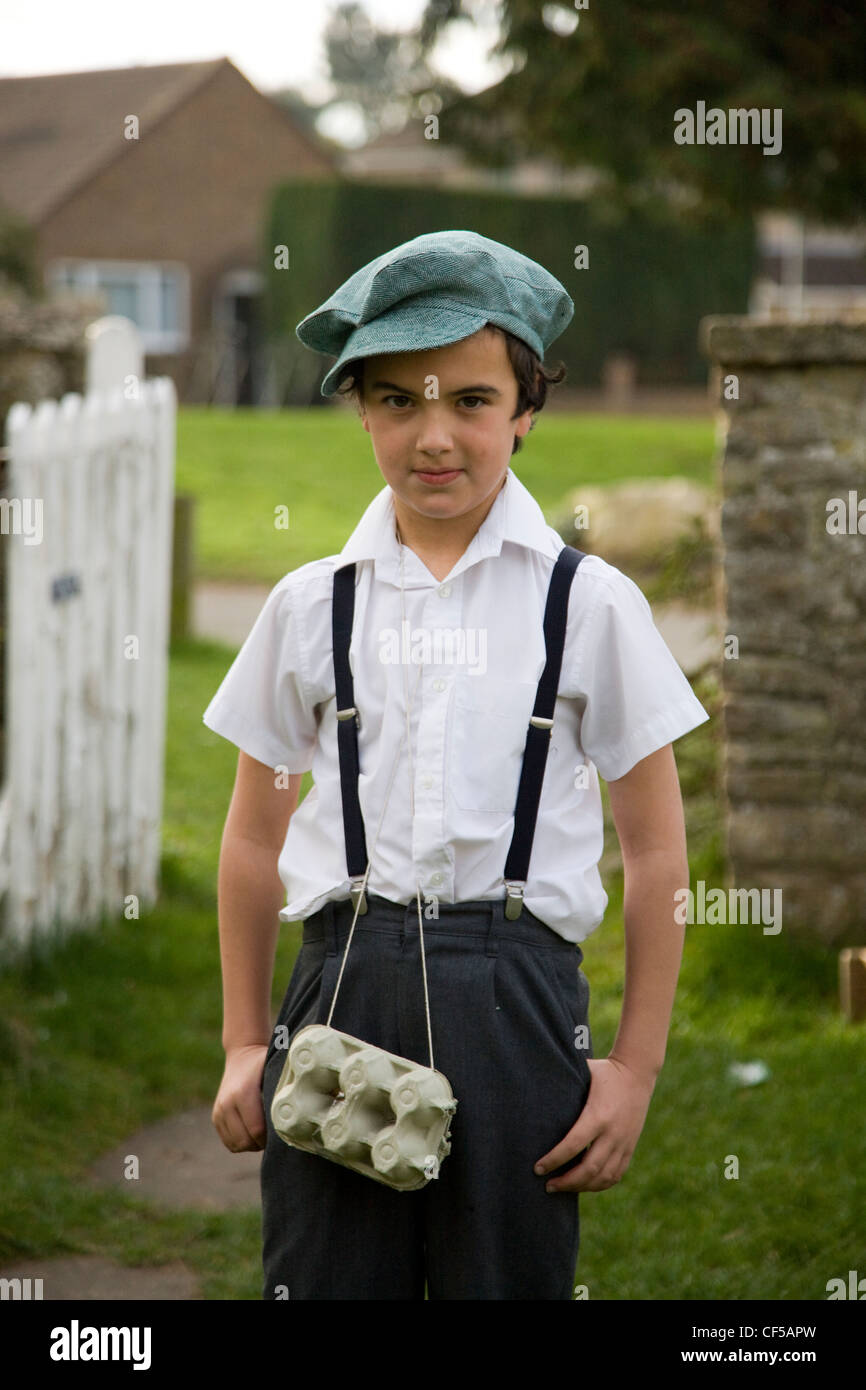 Schoolboy dressed in 1940s costume with egg box as gas mask