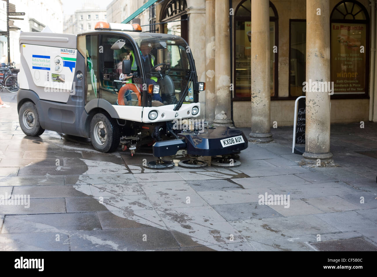 Street cleaning machine sweeping the pavement in Bath city centre, Somerset Stock Photo