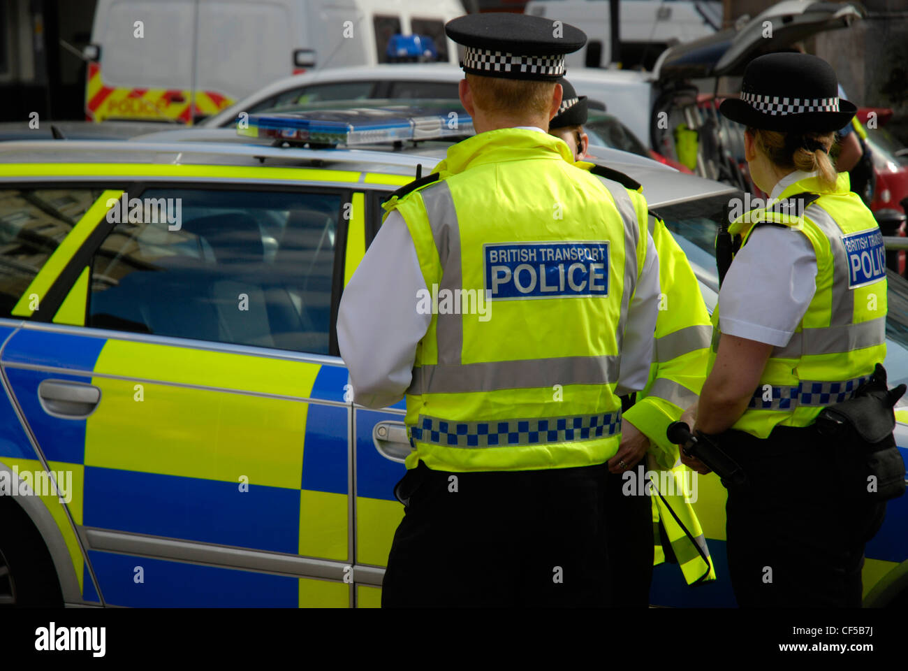British transport police officers in yellow jackets standing next to a police car in Westminster. - Stock Image