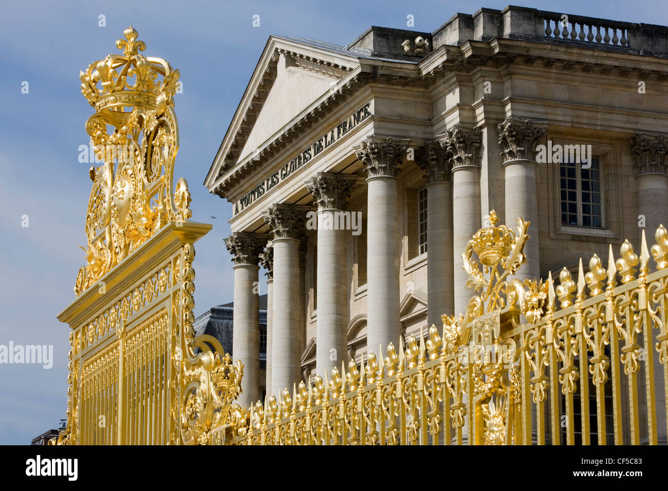 Gold gilded gates, colonnades and pediment at The Palace of Versailles, France - Stock Image
